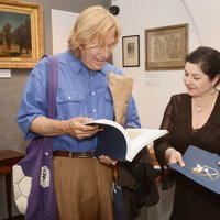 "Jolanta Pollesch presenting the ""A Gift of Beauty"" album to a visitor"