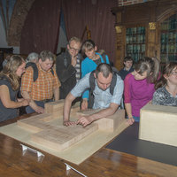 Visitors touching a mock-up of the Collegium Maius building